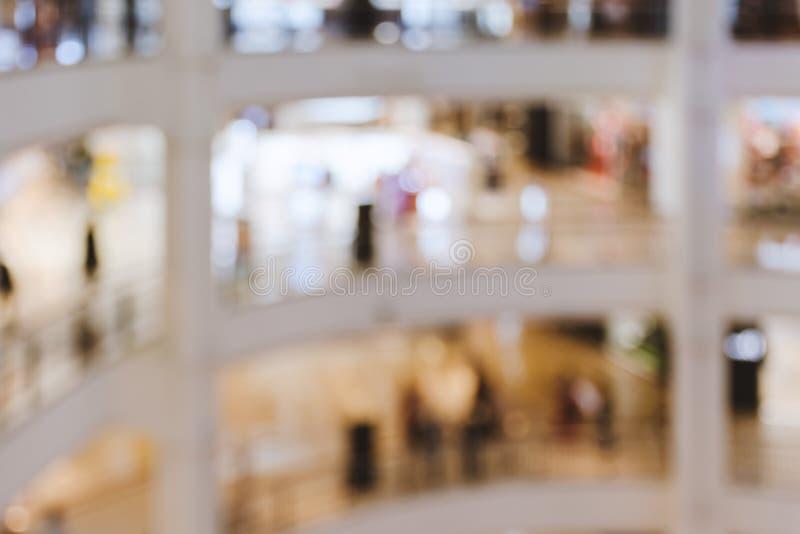 Unscharfes Bild, flache Schärfentiefe - Innenraum des großen mehrstöckigen Einkaufszentrums mit warmem Licht, Leute stockfotos