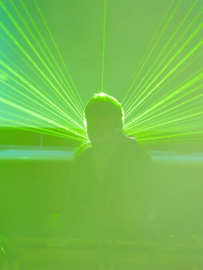 Unscharfes DJ in den grünen Laser-Strahlen stockfotografie