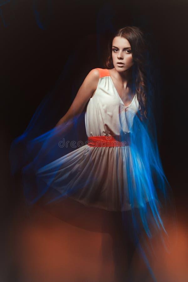 Unscharfes Farbkunstporträt eines Mädchens auf einem dunklen Hintergrund Arbeiten Sie Frau mit schönem Make-up und einem hellen S lizenzfreie stockfotografie