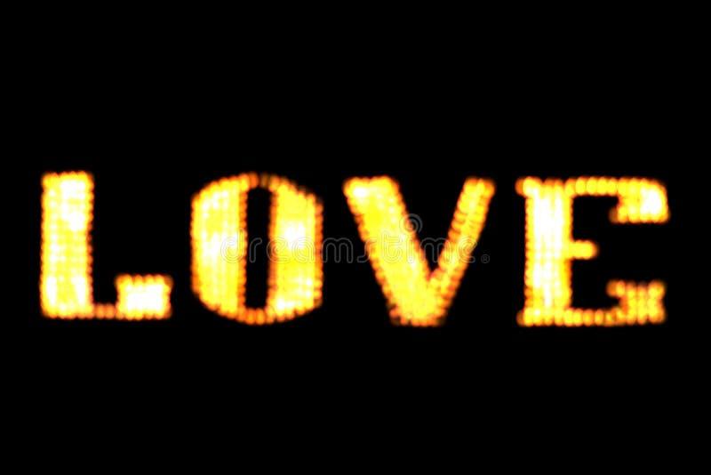 Unscharfes hellgelbes Gold des Text LIEBES-Zeichens LED Bokeh auf dunkler Wand, Neonlicht führte Buchstabe Liebe auf Hintergrunds lizenzfreie stockbilder