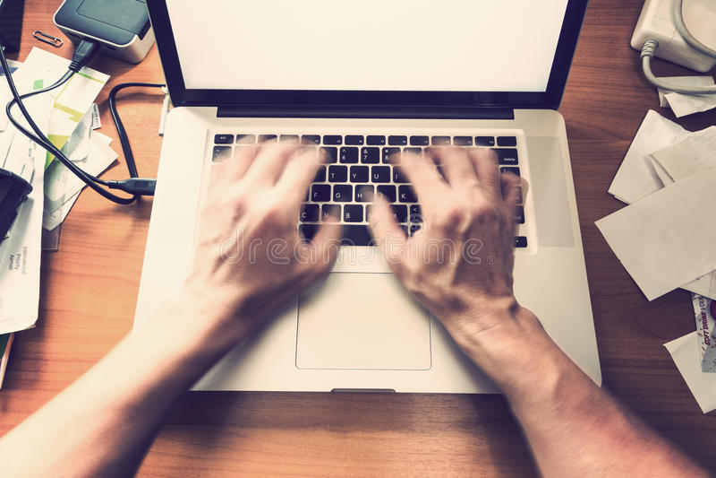Unscharfes männliches Handschreiben, arbeitend an Computertastatur auf beschäftigtem lizenzfreie stockbilder