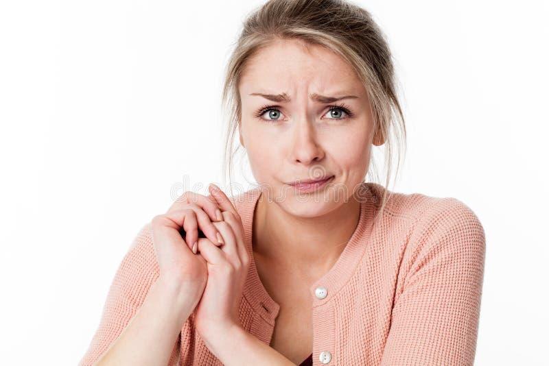 Unschuldige junge blonde Frau mit ihren Händen, die zusammen traurig sind stockfotografie