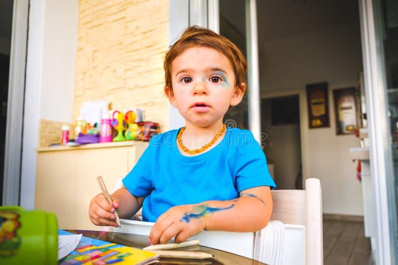 Unschuldiges Gesicht der boshaften Baby bluc Farbmarkierungen malte Kind stockbild