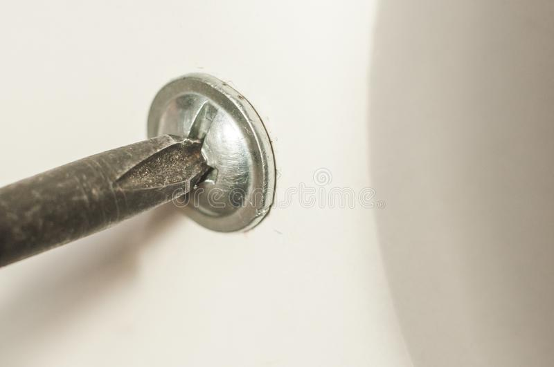 Unscrewing or twisting the bolt, self-tapping screw tie cross-head screwdriver.  stock photos