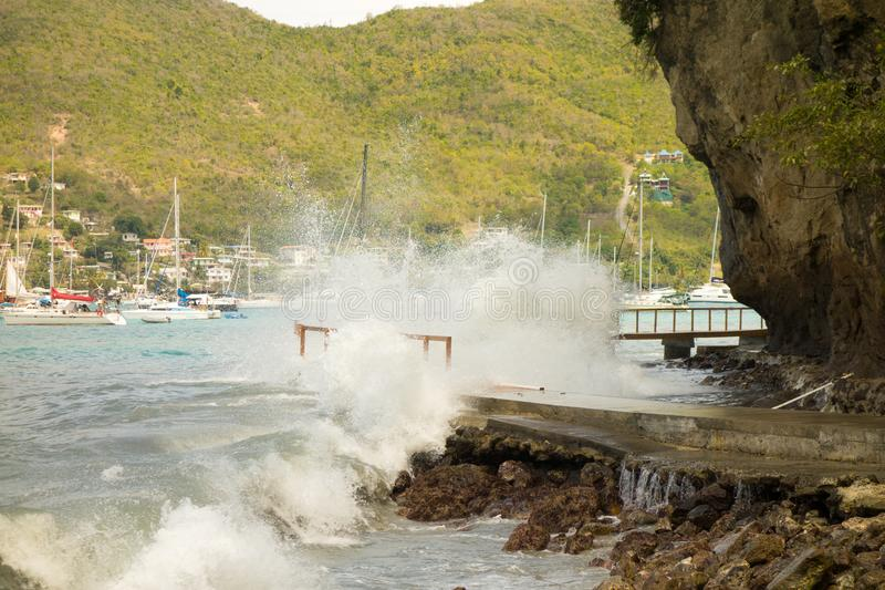 Unseasonal waves crashing against the shore in admiralty bay, bequia. A newly constructed walkway being demolished by a freak surge in the windward islands royalty free stock photography