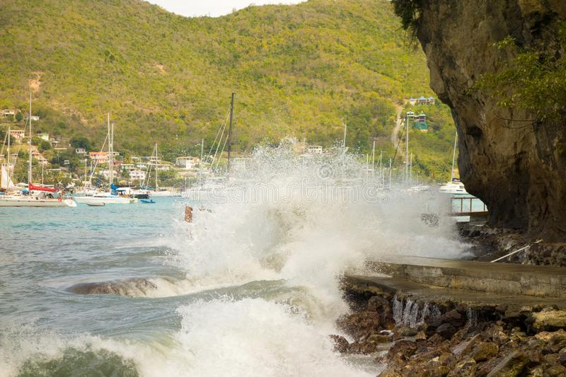 Unseasonal waves crashing against the shore in admiralty bay, bequia. A newly constructed walkway being demolished by a freak surge in the windward islands royalty free stock image