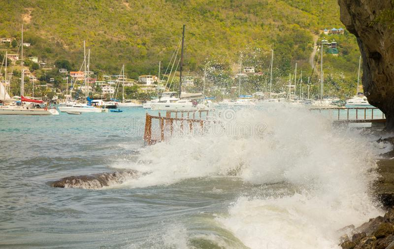 Unseasonal waves crashing against the shore in admiralty bay, bequia. A newly constructed walkway being demolished by a freak surge in the windward islands stock photos