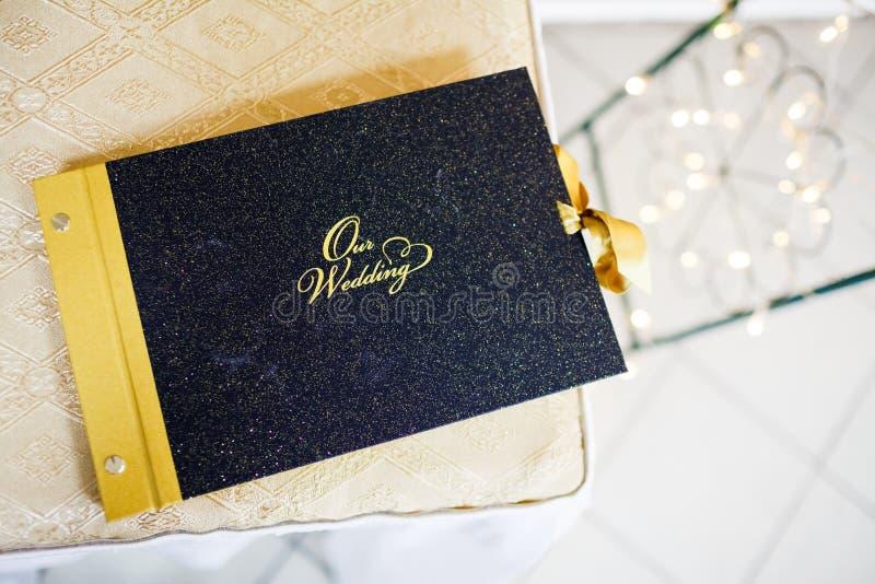 Unser Hochzeitsfotoalbum verziert mit Gold, photographische Geschichte des Tages lizenzfreie stockfotos