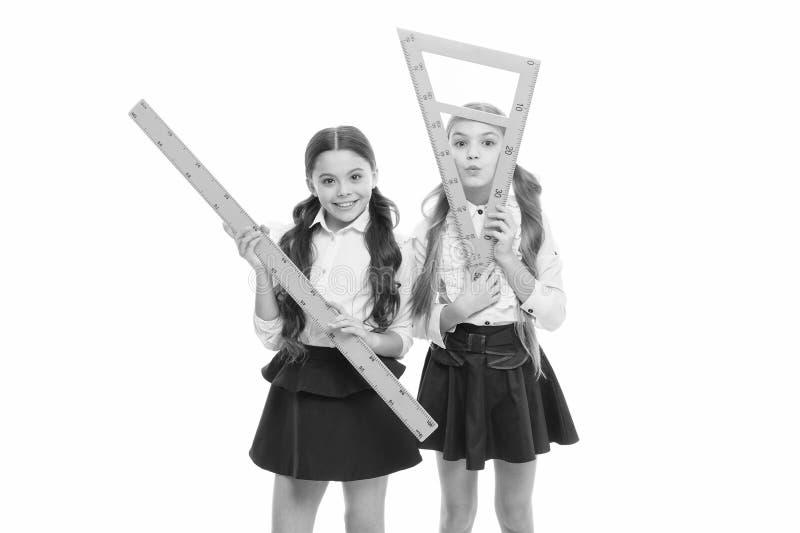 Unsere Lieblingsstunde Kleine Mädchen, die sich auf eine Lektion der Geometrie vorbereiten Cute schoolgirls, die dreieckig und Li lizenzfreie stockbilder