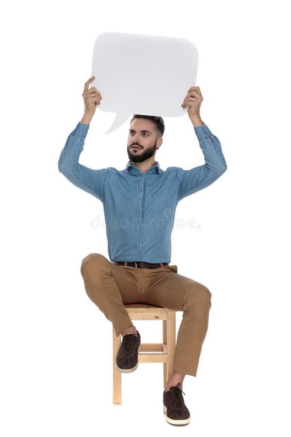 Unshaved человек сидя и задерживая пустой знак сообщения стоковое фото rf