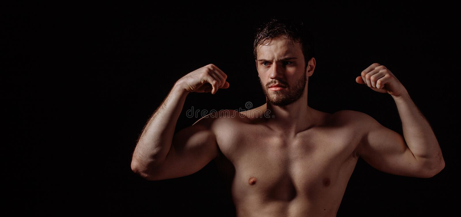 Unshaven bald bodybuilder with six pack is demonstrating his muscles. Isolated on the back background.being good at bodybuilding stock images