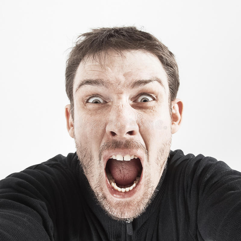 Unshaven man in a black jacket on a white background shouts stock image