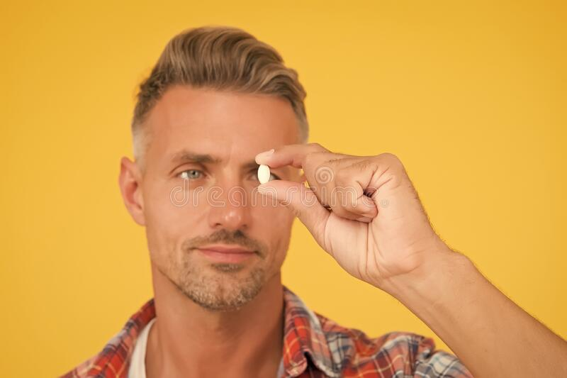 Unshaven man hold vitamin pill, selective focus. medicine concept. anabolic and steroids. food additives for male health. Bio vitamin complex. disease stock photography