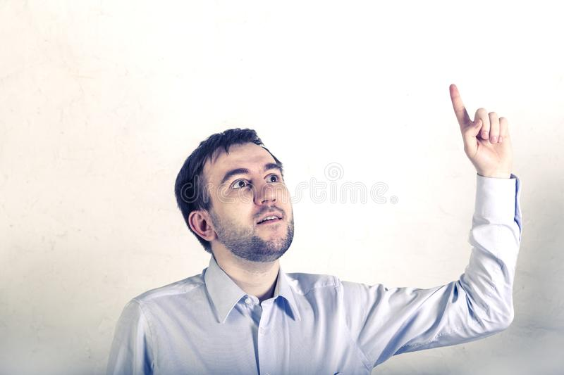 Unshaven young male programmer freelancer looks up and shows his finger-found a solution after thinking stock images