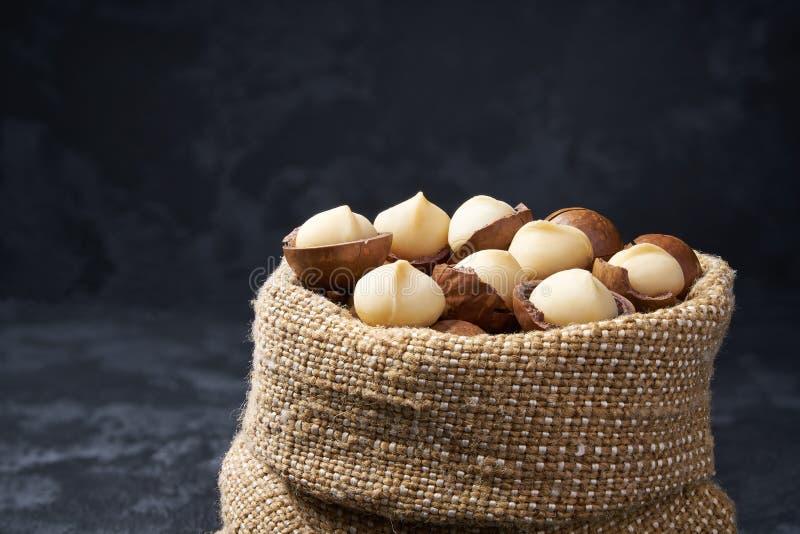 Unshelled macadamia καρύδια σε μια κινηματογράφηση σε πρώτο πλάνο τσαντών, στο μαύρο υπόβαθρο στοκ φωτογραφία