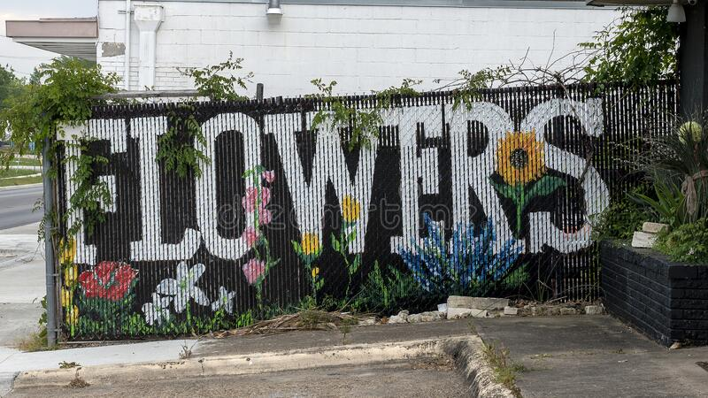 Unsigned artwork on a fence advertising a flower shop in Oak Cliff in Dallas, Texas. Pictured is an unsigned painting with advertising a flower shop in Oak stock photo