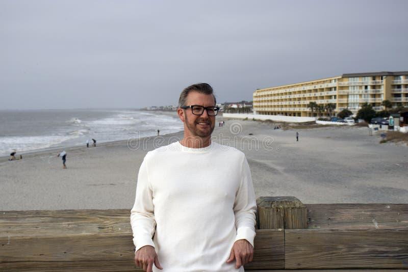 Unsinnigkeits-Strand South Carolina, am 17. Februar 2018 - weißes männliches Modell, welches das lange weiße Hemd sich lehnt am P lizenzfreie stockbilder