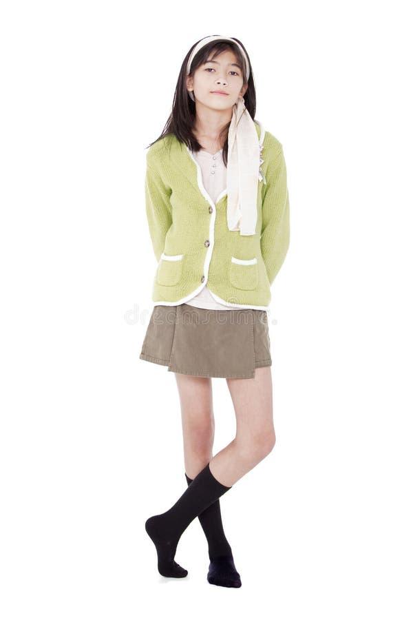 Unsmiling überzeugtes junges Mädchen in der grünen Strickjackestellung, isolat stockbild