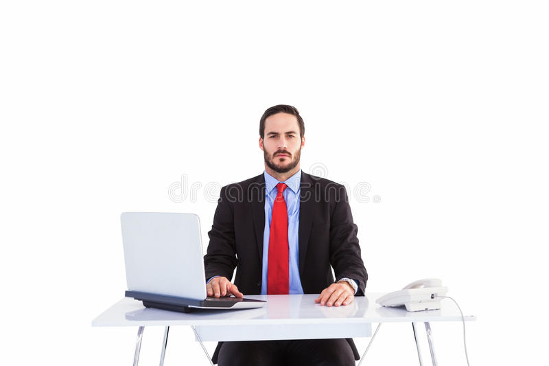 Unsmiling biznesmena obsiadanie przy biurkiem zdjęcie stock