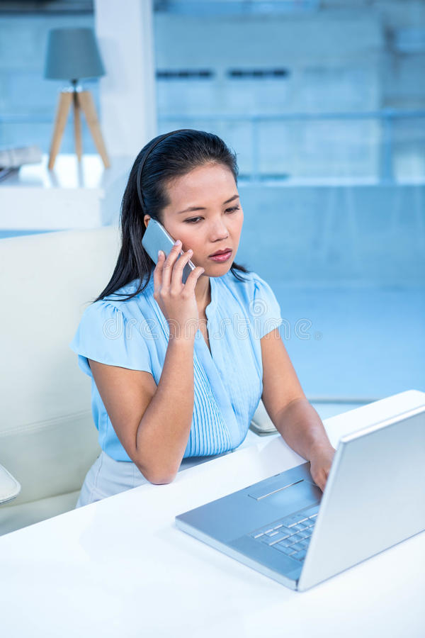 Unsmiling bizneswoman na telefonie używać laptop zdjęcie royalty free