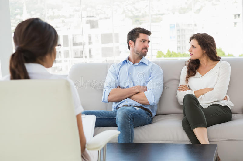 Unsmiling couple talking with their therapist. In the office royalty free stock images