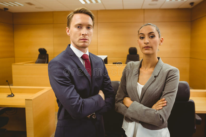 Unsmiling lawyers looking at camera crossed arms. In the court room stock image