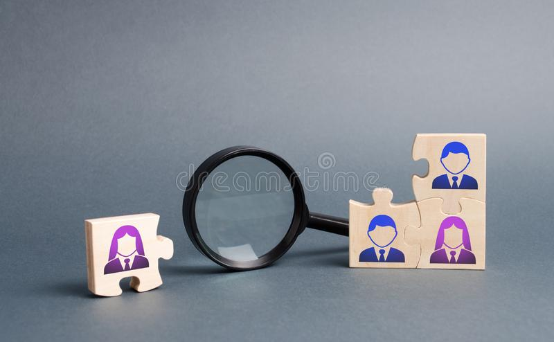 Unsorted team puzzle and magnifying glass. Search, recruitment staff, hiring leader. Lack of specialists in the labor market. Creating an efficient and royalty free stock photography