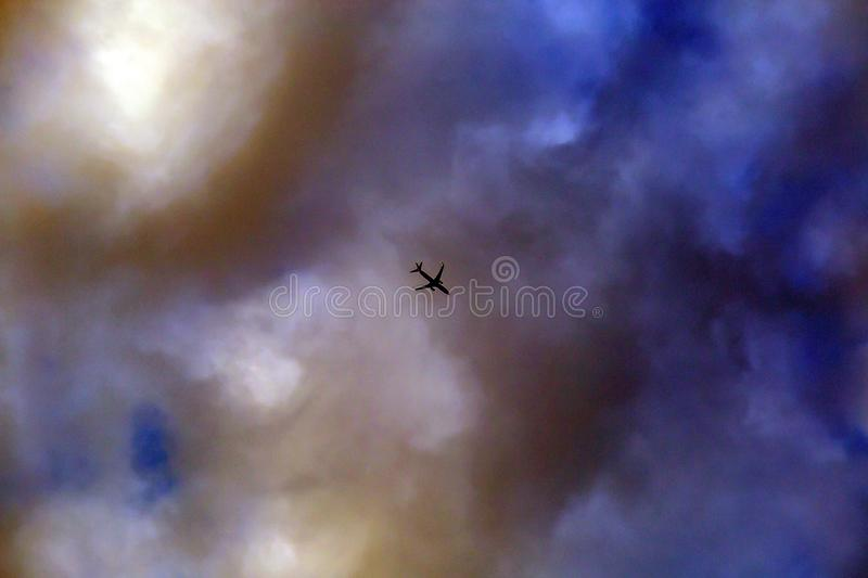 Unspecified airplane on the strange or storm clouds look danger. Stranger plane in cloud royalty free stock image