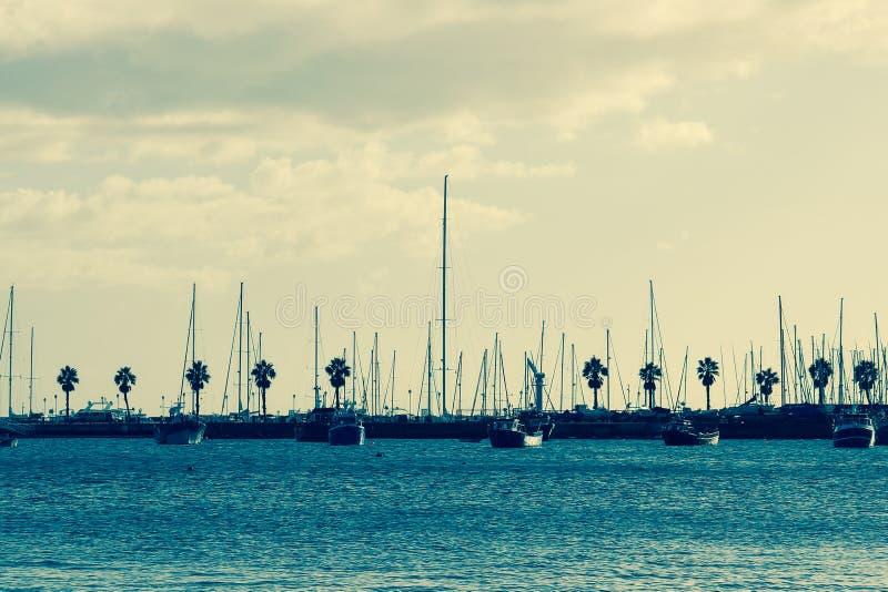 """unsplash com †""""błękitne wody oceanu żaglówek drzewka palmowe Chmurnieją obrazy stock"""