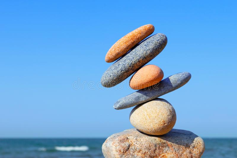 Unstable construction of multi-colored stones. The disturbed equilibrium. Imbalance concept royalty free stock image