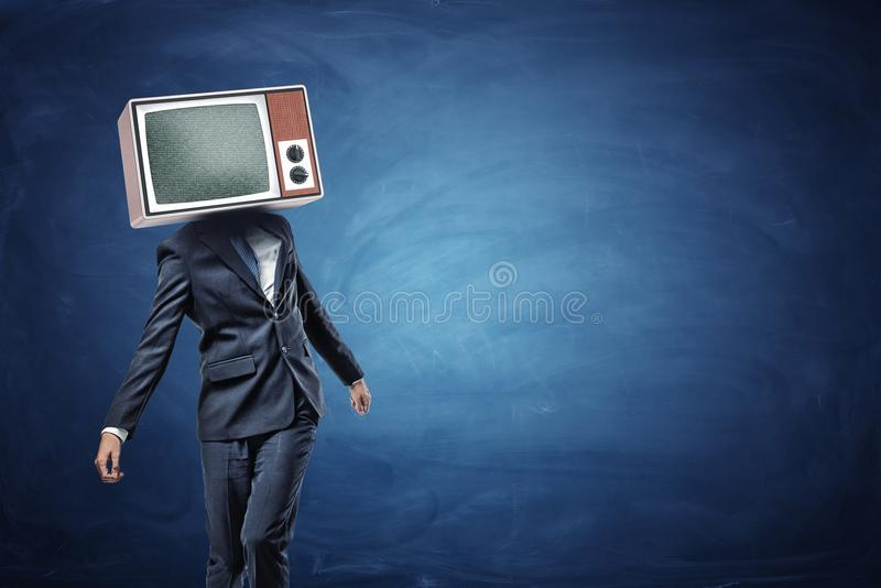 An unsteady businessman standing unevenly with a large retro TV on his head showing gray noise. royalty free stock photo