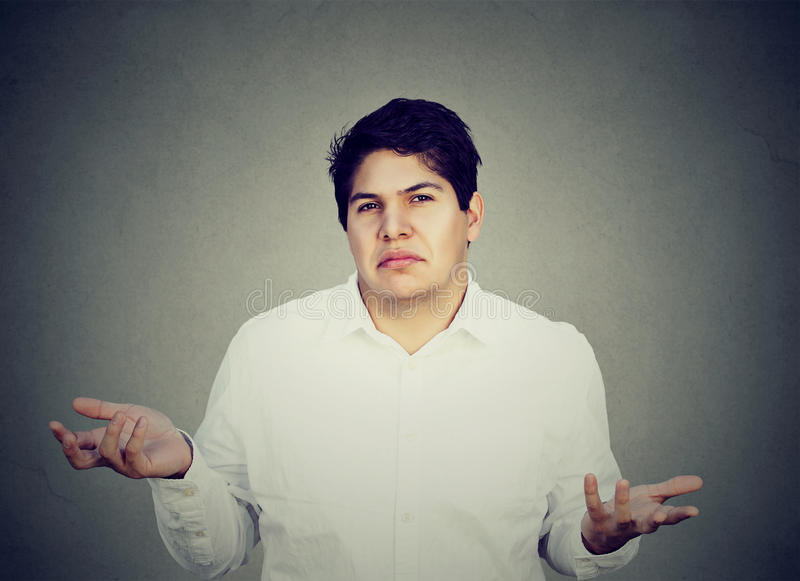 Unsure confused man shrugging shoulders. Portrait of unsure confused man shrugging shoulders isolated on gray background stock photography