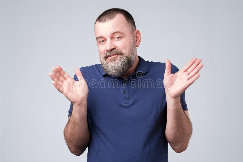 Bearded man in blue t-shirt shrugging shoulders. Unsure confused puzzled bearded man in blue t-shirt shrugging shoulders isolated over gray background stock photos