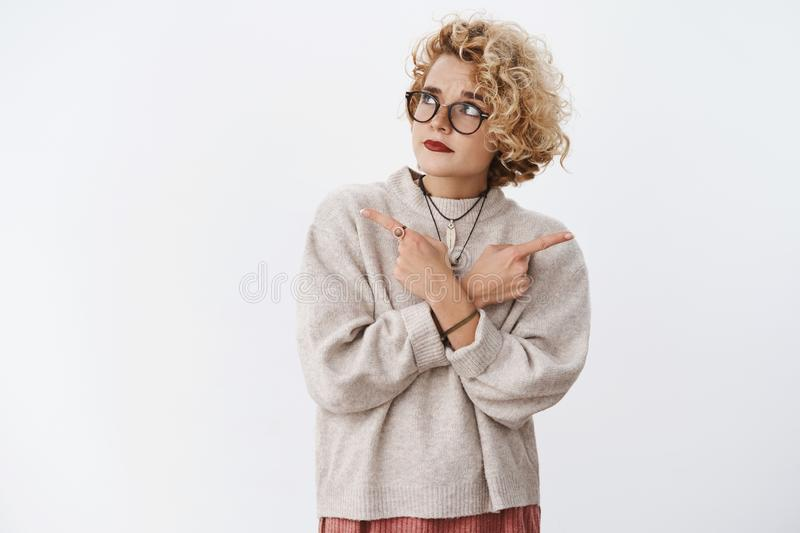 Unsure and hesitant cute questioned hipster female wearing glasses and makeup raising eyebrow doubtful looking. Suspicious and uncertain at upper left corner as royalty free stock image