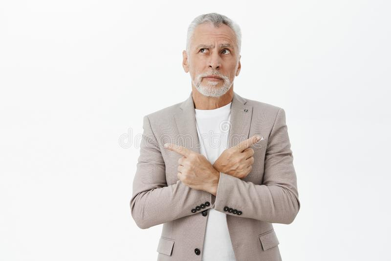 Unsure hesitant and questioned old businessman in grey suit with grey beard and hair crossing hands against chest. Pointing left and right looking up uncertain royalty free stock photos
