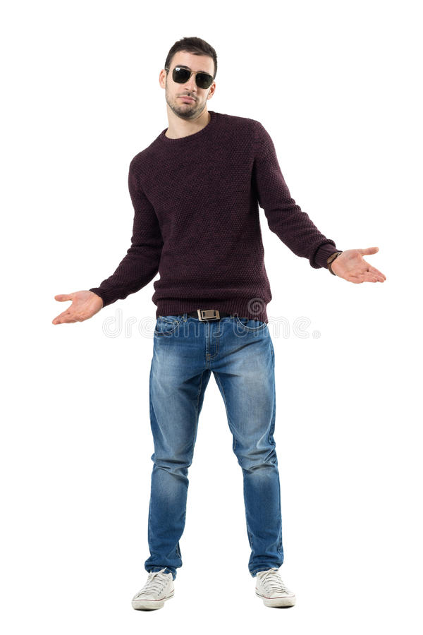 Unsure young man wearing sweater and sunglasses shrugging shoulders. Full body length portrait isolated over white studio background stock photography