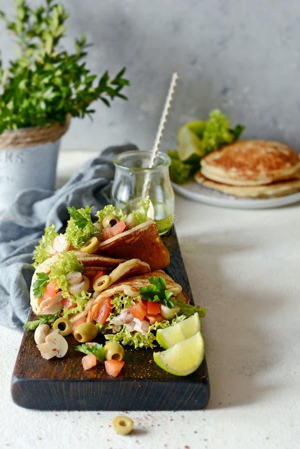 Unsweetened pannkakor med kalkon, grönsallat, tomater, inlagda champinjoner, oliv och gräsplaner i form av taco på ett träbräde royaltyfria bilder
