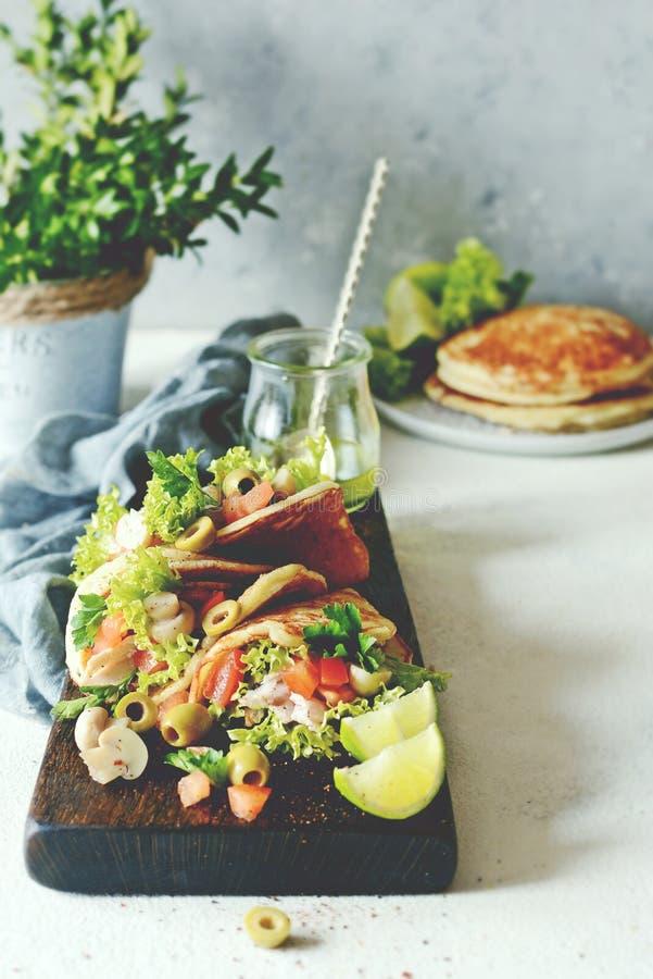 Unsweetened pannkakor med kalkon, grönsallat, tomater, inlagda champinjoner, oliv och gräsplaner i form av taco på ett träbräde royaltyfri bild