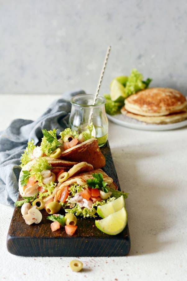 Unsweetened pannkakor med kalkon, grönsallat, tomater, inlagda champinjoner, oliv och gräsplaner i form av taco på ett träbräde arkivfoton
