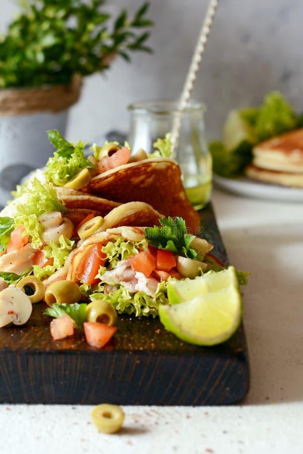 Unsweetened pannkakor med kalkon, grönsallat, tomater, inlagda champinjoner, oliv och gräsplaner i form av taco på ett träbräde royaltyfri fotografi