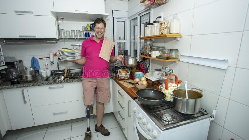 untauglich Mann ohne Bein Säubern der Küche stockbild