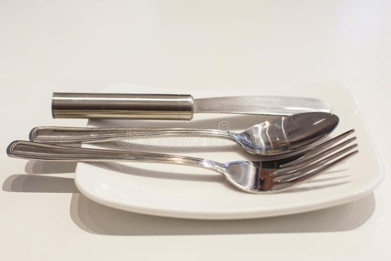 Unte con mantequilla el cuchillo, la bifurcación y la cuchara en una placa blanca imagenes de archivo