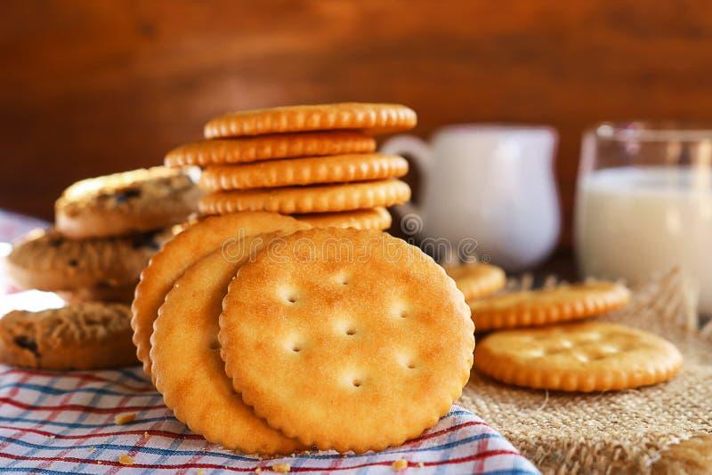 Unte con mantequilla las galletas galleta y la leche puso en servilleta y el CCB de madera imagenes de archivo