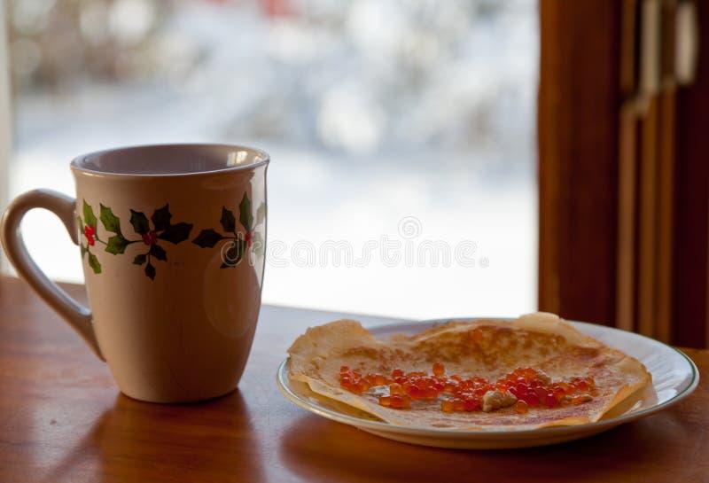 Unte con mantequilla los crespones smoothered con el caviar y la taza rojos de té caliente en la tabla de madera fotografía de archivo libre de regalías