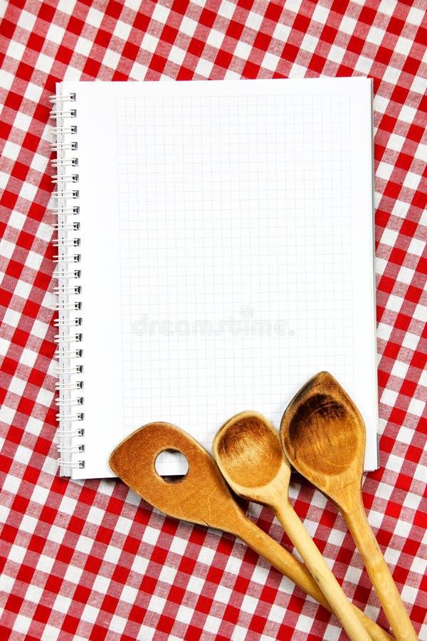 Untencil di cottura di legno e libro in bianco di ricetta immagini stock
