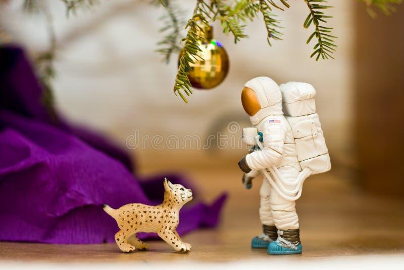Unter dem Baum Luchs, der einen Astronauten betrachtet orange, rot, Grüngelb - vector- Nachricht Spielzeug minifigures lizenzfreie stockfotos