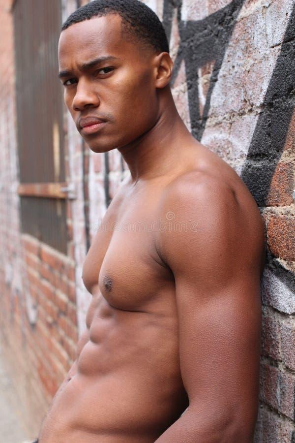 Unter dem Sonnenschein steht ein männlicher schwarzer Kerl, halb nackt, eine Gasse mit rauem Ausdruck bereit lizenzfreie stockbilder