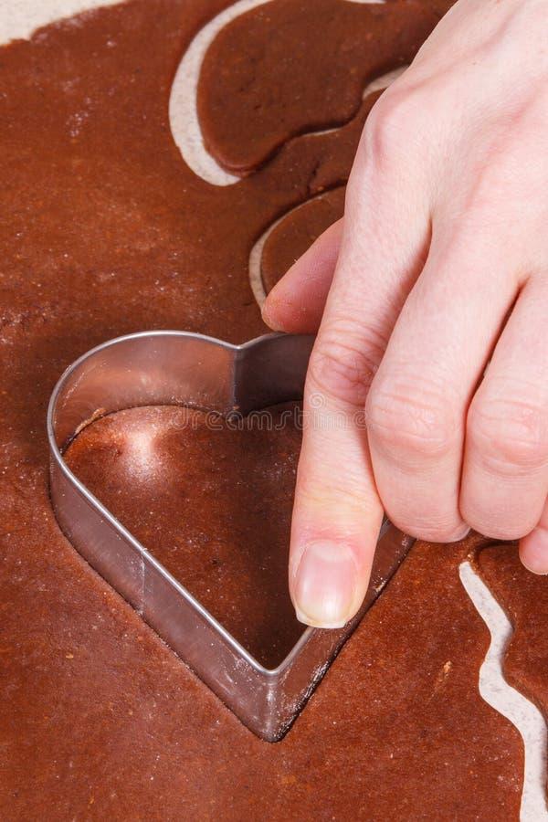 Unter Verwendung der Plätzchenschneider in Form des Herzens für das Backen von festlichen Plätzchen oder von Lebkuchen, Weihnacht lizenzfreie stockfotos