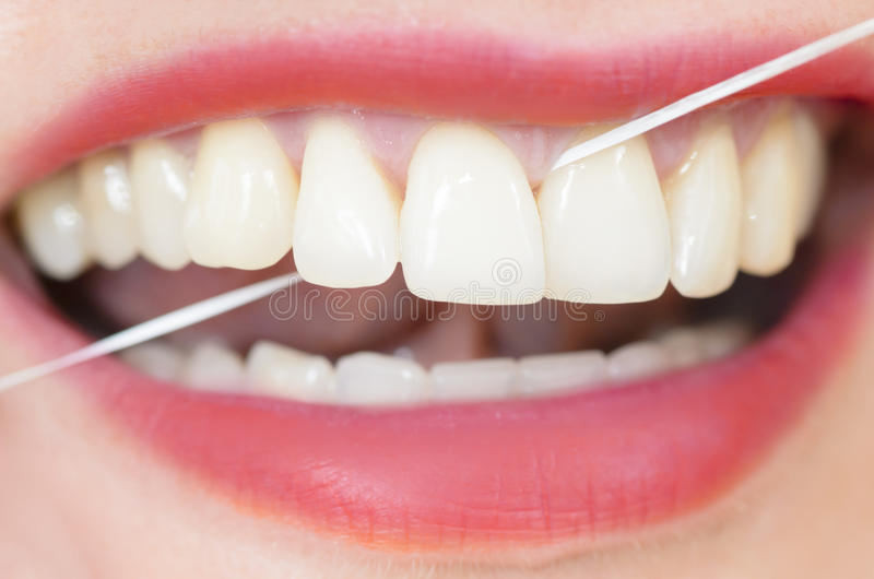 Unter Verwendung der Zahnseide lizenzfreie stockfotografie