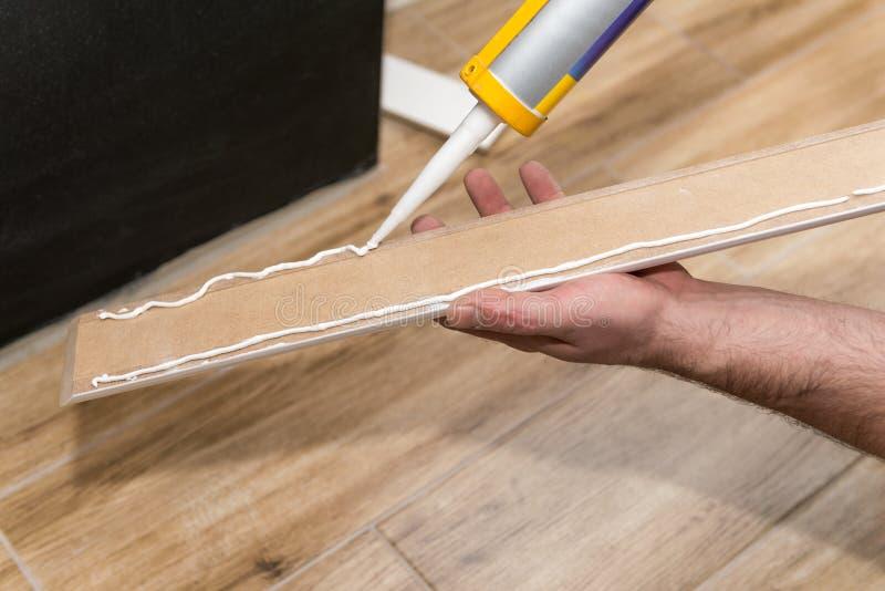Unter Verwendung des Abdichtengewehrs, zum der weißen Fussleiste zu installieren lizenzfreie stockfotografie